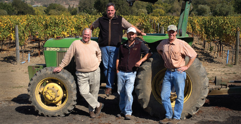 Tractor & four men. Corley vineyards in the background.